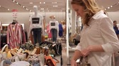 vitrin : Girl talking on the phone in a clothing store Stok Video