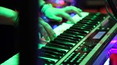 zábava : Female hands playing electric piano under colorful stage lighting, close-up.