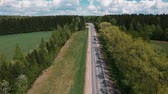 hlavička : The drone flies over the road between the trees and watching the cars