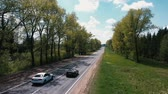kopbal : The drone flies over the road between the trees and watching the cars