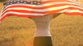 cabelos cacheados : 4K video clip of mixed race African American girl teenager female young woman holding an American USA Stars and Stripes flag in a wheat field at sunset or sunrise