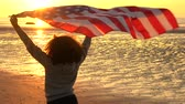 cabelos cacheados : 4K jib crane video clip of mixed race African American girl teenager female young woman holding an American US Stars and Stripes flag on a beach at sunset or sunrise Vídeos