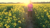 flor cabeça : 4K video clip of beautiful healthy mixed race African American girl teenager female young woman running or jogging and drinking a bottle of water in field of yellow flowers