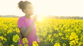 řepkový : 4K video clip of beautiful healthy mixed race African American girl teenager female young woman running or jogging and drinking a bottle of water in field of yellow flowers