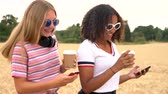 Slow motion tracking video clip of pretty blonde girl and mixed race teenager young women wearing sunglasses drinking coffee and using mobile cell phones