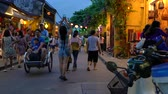 LOCAL PEOPLE AND TOURISTS AT NIGHT ON THE STREETS OF HOI AN, VIETNAM – 6 APRIL 2018: Local people, tourists and bicycle rickshaws at night on the streets of Hoi An, Vietnam Stock mozgókép