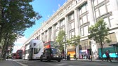 SELFRIDGES DEPARTMENT STORE, OXFORD STREET, LONDON, ENGLAND – 25 SEPTEMBER 2018: Slow moving queuing traffic, taxis and red double decker London buses driving past Selfridges, Oxford Street, London, England Stock mozgókép