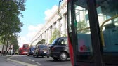 SELFRIDGES DEPARTMENT STORE, OXFORD STREET, LONDON, ENGLAND – 25 SEPTEMBER 2018: Slow moving queuing traffic, taxis and red double decker London buses driving past Selfridges, Oxford Street, London, England