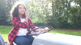 Beautiful African American mixed race teenage girl young woman driving a gray tractor through a sunny apple orchard eating an apple