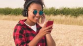 Slow motion tracking video of beautiful mixed race African American girl teenager young woman wearing a red and black shirt and blue sunglasses listening to music on her cell phone and wireless headphones