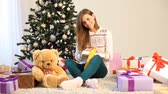 świeca : the girl sitting by the Christmas tree and Christmas gifts