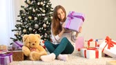 presentes : the girl sitting by the Christmas tree and gifts opens
