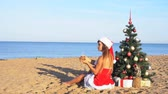 carry : girl on beach resort in Christmas clothes for the new year in the tropics 1 Stock Footage