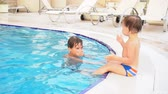 potomstvo : two boys brother bathe in the swimming pool at the resort