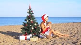 Санта шляпе : girl on beach resort in Christmas clothes for the new year in the tropics Стоковые видеозаписи