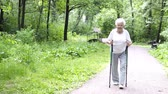 chignon : grandmother walks with Nordic walking sticks Vidéos Libres De Droits
