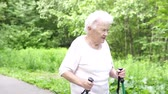 wandelstok : grandmother walks with Nordic walking sticks Stockvideo
