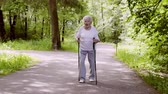 vôo : Grandma walks in the park with sticks for Nordic walking