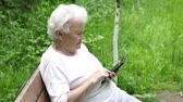 ágy : old granny looks at Internet smartphone Stock mozgókép