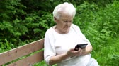 grateful : old granny looks at Internet smartphone Stock Footage