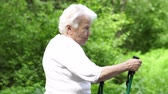 pensioner : grandmother walks with Nordic walking sticks old grey