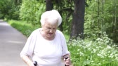 suéter : grandmother walks with Nordic walking sticks old grey