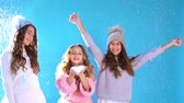 three beautiful girls in a hat play in the snow Stockvideo