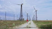 vaquera : Woman near working wind farm Archivo de Video