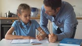 working parents : Father helping daughter with homework at home.