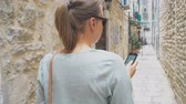 sýkorka : Female tourist with mobile phone lost in the old town.