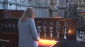 rouw : Woman holding candle near altar in church.