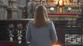 simbolismo : Woman holding candle near altar in church.