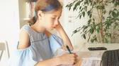 iskoláslány : Little girl doing homework at home.