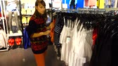 társult : Shopping in outlets Europe. The girl chooses clothes. Sale and discounts.