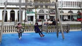 glaze : LA CORUNA, SPAIN - APRIL 2, 2018: Children at the playground on the city embankment. La Coruna the largest city in the northwest of Spain, the resort and the port. Slow motion. Stock Footage