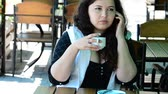 cafe na : Communication behind a cup of coffee. The girl in cafe with phone