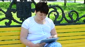sólido : The girl in the park on the bench with the tablet