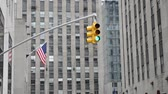 red traffic light : New York. Traffic lights and flag of the USA, against skyscrapers. Stock Footage