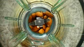 karma : Crushing of almonds in the blender. Slow motion. Knives crush almonds. Top view. Stok Video