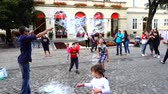 enfants jeux : LVIV, UKRAINE - AUGUST 3, 2019: The unknown man lets soap bubbles for children to squares of the city. Slow motion.