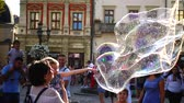 enfants jeux : LVIV, UKRAINE - AUGUST 25, 2019: An unknown man entertains children with soap bubbles in the city square. Slow motion. Vidéos Libres De Droits