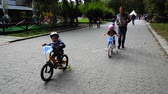 faaliyetler : LVIV, UKRAINE - SEPTEMBER 21, 2019: Children s cycling in the city park. Slow motion.