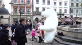 hagyományos kultúra : LVIV, UKRAINE - DECEMBER 15, 2019: Street artist in the clothes of a huge polar bear entertain the public in the square of the city. Stock mozgókép
