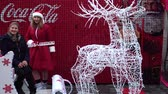 szánkó : LVIV, UKRAINE - DECEMBER 21, 2019: Unknown people are photographed with deer and sleigh against the background of Coca-Cola Christmas advertisement.