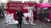 carbonatadas : LVIV, UKRAINE - DECEMBER 21, 2019: Unknown people are photographed with deer and sleigh against the background of Coca-Cola Christmas advertisement.