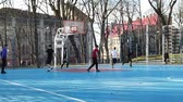 LVIV, UKRAINE - FEBRUARY 22, 2020: Teenagers play basketball at the city sports ground in the public square. Videos