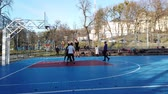 basketbal : LVIV, UKRAINE - FEBRUARY 22, 2020: Teenagers play basketball at the city sports ground in the public square. Stockvideo