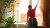wet : Girl washes the window in the kitchen at home, view from the back