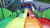 deslize : Small children ride a sliding board at an amusement park