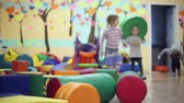 color : Children play in the playroom, soft toys scattered on the floor